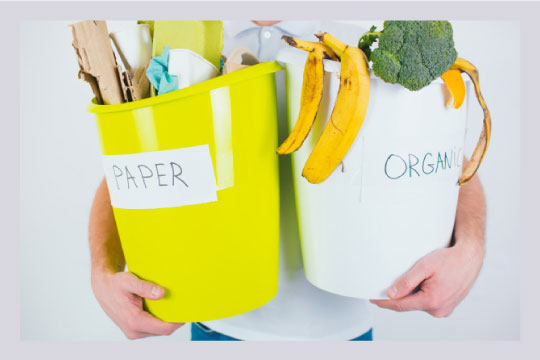 A man standing with two bins of segregated waste labelled paper and organic respectively.